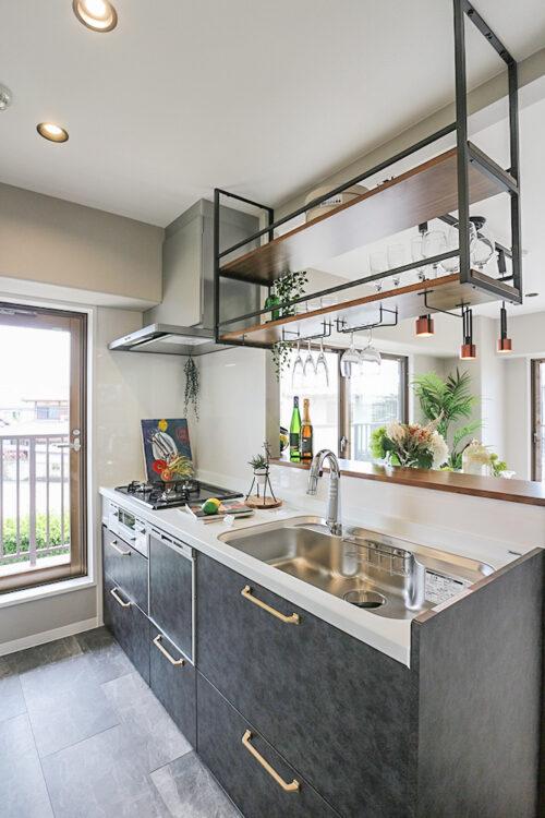 対面式のシステムキッチン。カフェバーのような吊り棚を設置し、お気に入りの食器やワインを収納出来ます。キッチンには食器洗い乾燥機付き。(2021年6月)撮影