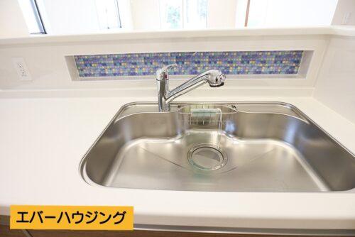 キッチンの水洗い場には水色のモザイクタイル柄のワンポイントがあります。